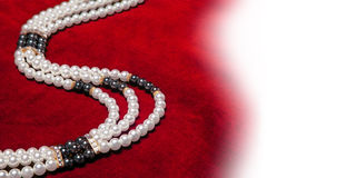 Pearl necklace (with space for your text or logo). Pearl necklace on red velvet Royalty Free Stock Images