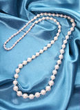 Pearl necklace on turquoise silk fabric Stock Image