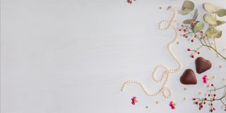 Pearl necklace, two cookies in form of heart and dogrose on light gray background. Stock Photo