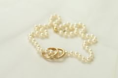 Pearl necklace with two golden rings Stock Photo