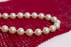 Pearl necklace. White pearl necklace on the maroon background Stock Photography