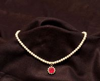 Free Pearl Necklace With Red Ruby Stone In Black Background Stock Image - 29363251