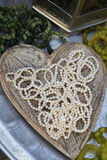 A pearl necklace in a wooden heart shaped bowl Stock Image