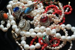 Pearl necklaces and rings with glasses from India. Pearl chains and rings with coloures glass such as Swarovsky look liked as rubin and sapphire. From India stock photo