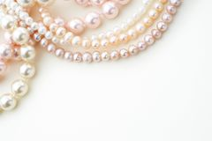 Pearl jewelry with copy space. Pearl necklaces in white and pink on paper background with copy space Stock Photo