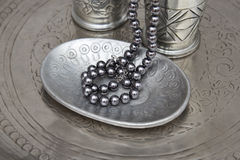 Pearl necklet and a plate Royalty Free Stock Photos
