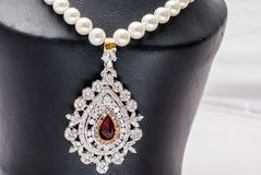 Pearl neclace with a pendany. Pearl necklace with a big pendant and large ruby stock photo
