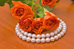 Pearl neclace and red roses Royalty Free Stock Images