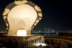 Pearl & Oyster, Corniche, Doha, Qatar at Night. The Pearl and Oyster fountain on the Corniche in Doha, Qatar at night. The Doha skyline is visible in the Stock Photo