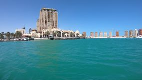 The Pearl Qatar Harbor. Doha, Qatar - February 18, 2019: Marina corniche promenade in Porto Arabia at the Pearl-Qatar with residential towers and luxury boats stock footage
