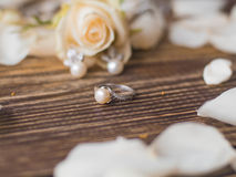 Pearl ring on beautiful wooden background with rose. close up Royalty Free Stock Photos