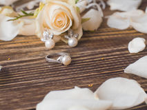 Pearl ring and earrings with white rose on dark wooden background, close up Stock Image