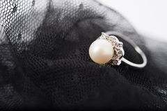 A pearl ring on the lace fabric. Can be used as background of jewellry or wedding Royalty Free Stock Photography