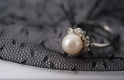 A pearl ring on the lace fabric. Can be used as background of jewellry or wedding stock image