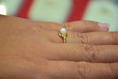 Pearl ring on pretty fingers. Fingers wearing a pearl ring surrounded by beautiful diamonds adds beauty to your hands Stock Image