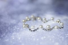 Pearl silver bracelet with diamonds on a blurry blue background.  Royalty Free Stock Image