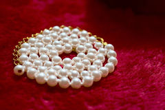 Pearl spiral necklace on plush red material Stock Images