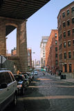Pearl Street, DUMBO, Brooklyn, NYC, USA. Cobblestoned Pearl Street, Down Under the Manhattan Bridge Overpass (DUMBO). Empire State Building is seen distant royalty free stock photo