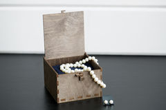 Pearl in a wooden box. On a black and white background royalty free stock photos