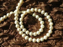Pearls. Natural white pearls on the brown fabric Stock Photography