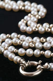 Pearls. Long string of pearls with gold beads and a gold clasp on a black background Royalty Free Stock Images