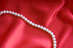 Pearls. On a red silk fabric Stock Image