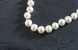Pearls. Strand of pearls on a hard slate background Stock Photo