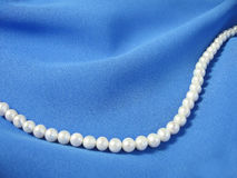 Pearls on background the blue fabric Stock Photos