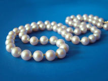 Pearls on Blue. String of pearls on blue background stock photography