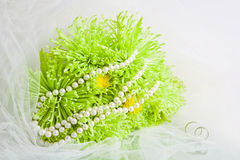 Pearls and bouquet of green chrysanthemums. White necklace of pearls and bouquet of green chrysanthemums on a white veil Stock Photo