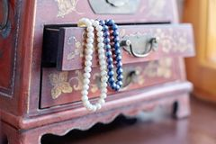 Pearls in a box. Two necklaces white and lilac pearls in opened vintage case with beautiful ornaments on wooden surface. Indoors, copy space royalty free stock photography