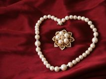 Pearls and brooch. Heart-shaped string of pearls around a pearl brooch royalty free stock images