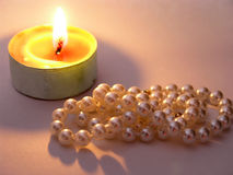 Pearls in candle light. Pearls in warm candle light with DOF blur on candle stock images