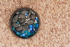 Pearls and colored stones in clay vase on carpet background. Stock Images