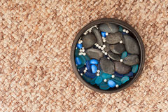 Pearls and colored stones in clay vase on carpet background. Royalty Free Stock Photography