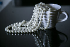 Pearls in cup. Pearls in coffee cup with nice reflection on the table Royalty Free Stock Photo