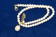 Pearls and Diamonds on Velvet. A pearl necklace with diamonds on blue velvet Stock Image