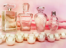 Pearls and different bottles of perfume on lighte pink backgroun. D. Horizontal Stock Photos
