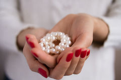 Pearls in female hands. With red manicure Stock Photos