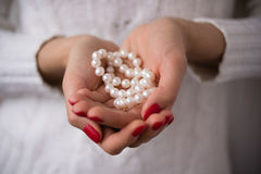 Pearls in female hands. With red manicure Royalty Free Stock Image