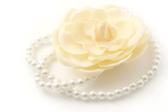 Pearls and flower. Macro shot of a beautiful flower and pearl necklace isolated on white Stock Images