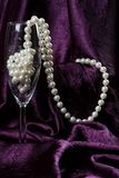 Pearls in Flute. Pearls in Champagne flute on purple background Royalty Free Stock Photo