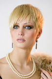 Pearls and furs. Portrait of a young girl with a short haircut with the ornament of pearls Royalty Free Stock Image