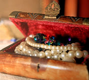 Pearls and gemstones. Inside a hand carved jewelry box Stock Photography