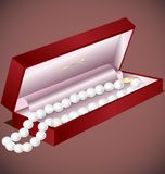 Pearls gift. In a decorative red box pearl beads Royalty Free Stock Photos