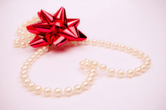 Pearls heart and red bow Stock Images