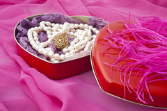 Pearls in a heart-shaped box. On a pink background Stock Photo