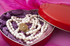 Pearls in a heart-shaped box. On a pink background Stock Photography