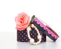 Pearls inside open gift box with pink rose Royalty Free Stock Photo