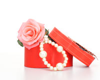 Pearls inside open gift box with pink rose. On white background Royalty Free Stock Image